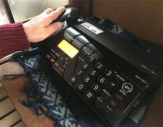 固定電話の受話器に手を掛ける女性。「還付金がある」といううその電話がここにかかってきた