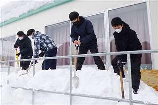 施設の避難経路にたまった雪を寄せる六郷高の生徒たち=1月21日、美郷町六郷の特別養護老人ホーム・ロートピア緑泉
