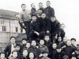 木造の一日市小校舎を背に同級生らと(後列右から4人目)=昭和33年ごろ