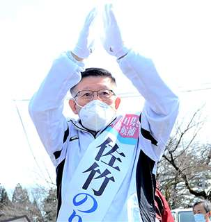 遊説中に声援を受け、両手を上げて応える佐竹候補=20日、美郷町