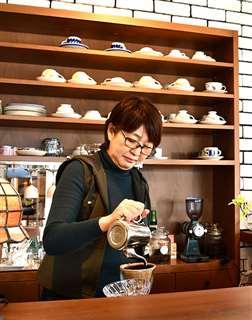 カフェのカウンターに立ち、コーヒーを入れる吉尾さん