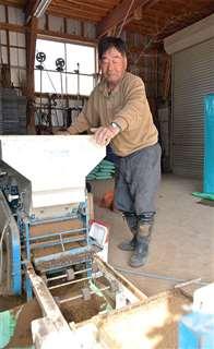 自動播種機の様子を確認する今野さん。ハウスを使わない育苗に挑戦する