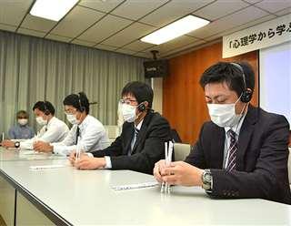 作業を指示する音声をヘッドホンで聞きながら鉛筆を立てる島根県警職員=2020年11月、島根県警本部
