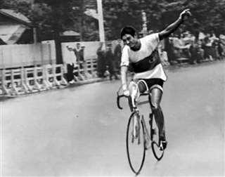 自転車の団体ロードレースで手を振って応援に応える加藤