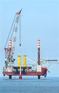 能代港湾区域内で洋上風車のモノパイル(中央)の打設工事を行うSEP船=12日午前9時40分ごろ