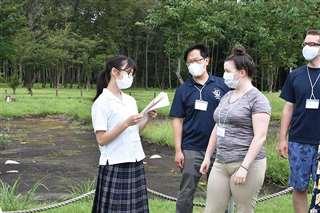 外国語指導助手に英語で伊勢堂岱遺跡について説明するジュニアボランティアガイド(左)=2020年8月17日