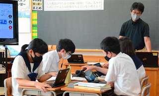 グループで話し合う生徒たちと児玉教諭