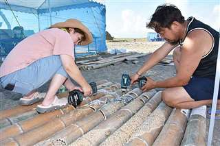 砂像のライトアップに使う竹に穴を開ける実行委員会のメンバー