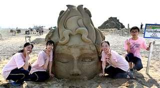 海から陸に上がろうとする女の子の砂像を制作した秋田美大付属高等学院の(左から)遠藤さん、棚木さん、相澤さん、菅原さん