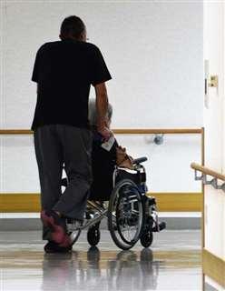 車いすの利用者を介助する職員。介護現場では慢性的な人材不足が続く